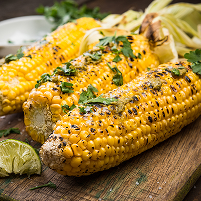 Grilled corn dressed with fresh pepper and herbs with a lime