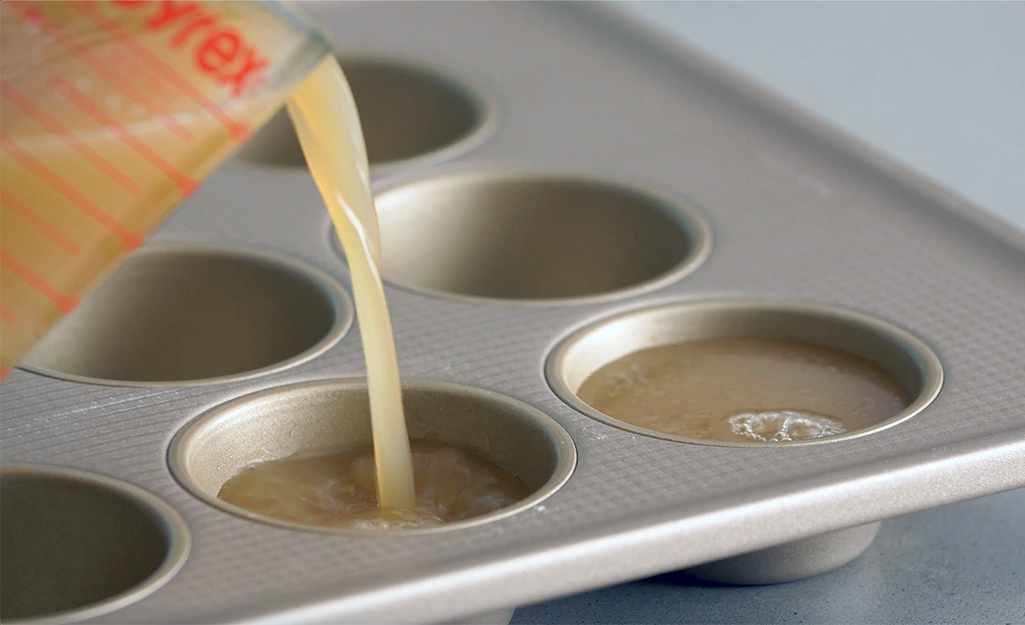 Someone pouring chicken broth in to muffin tin for freezing.