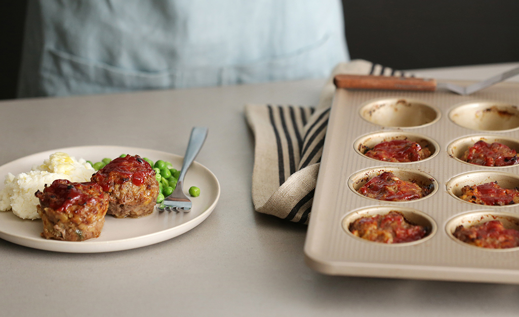 Mini meatloaves on a plate sitting beside a tin of mini meatloaves ready to go into the oven