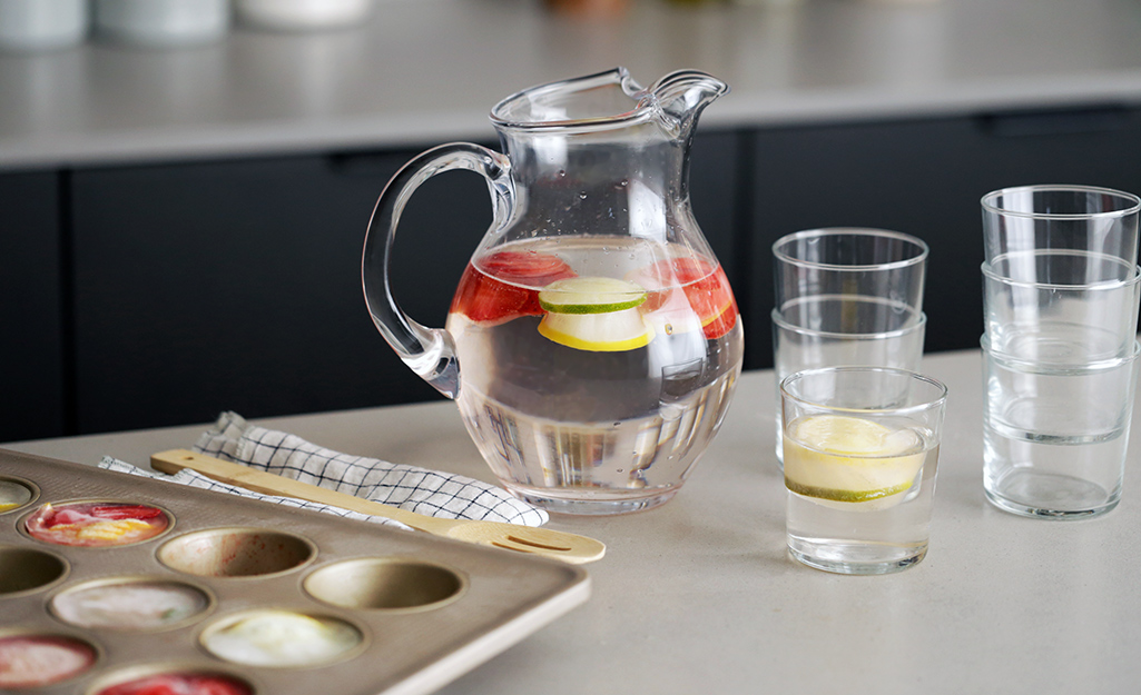 Muffin-sized fruity ice cubes floating in a glass pitcher.