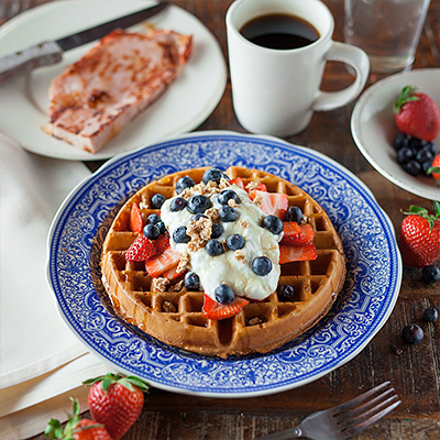 A cooked waffle topped with fruit on a plate.