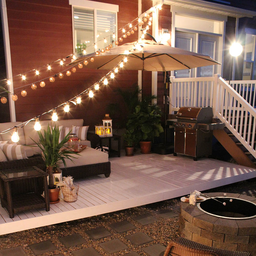 A backyard deck draped with string lights.