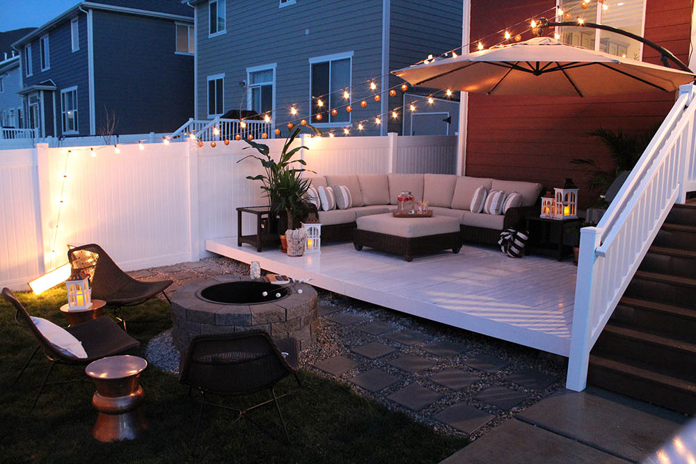A backyard deck with seating area next to a patio with a fire pit.