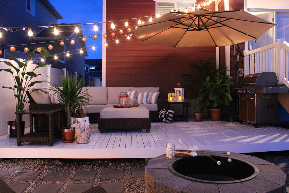 A white patio deck at night with string lights, outdoor seating, an umbrella, greenery, and a grill.