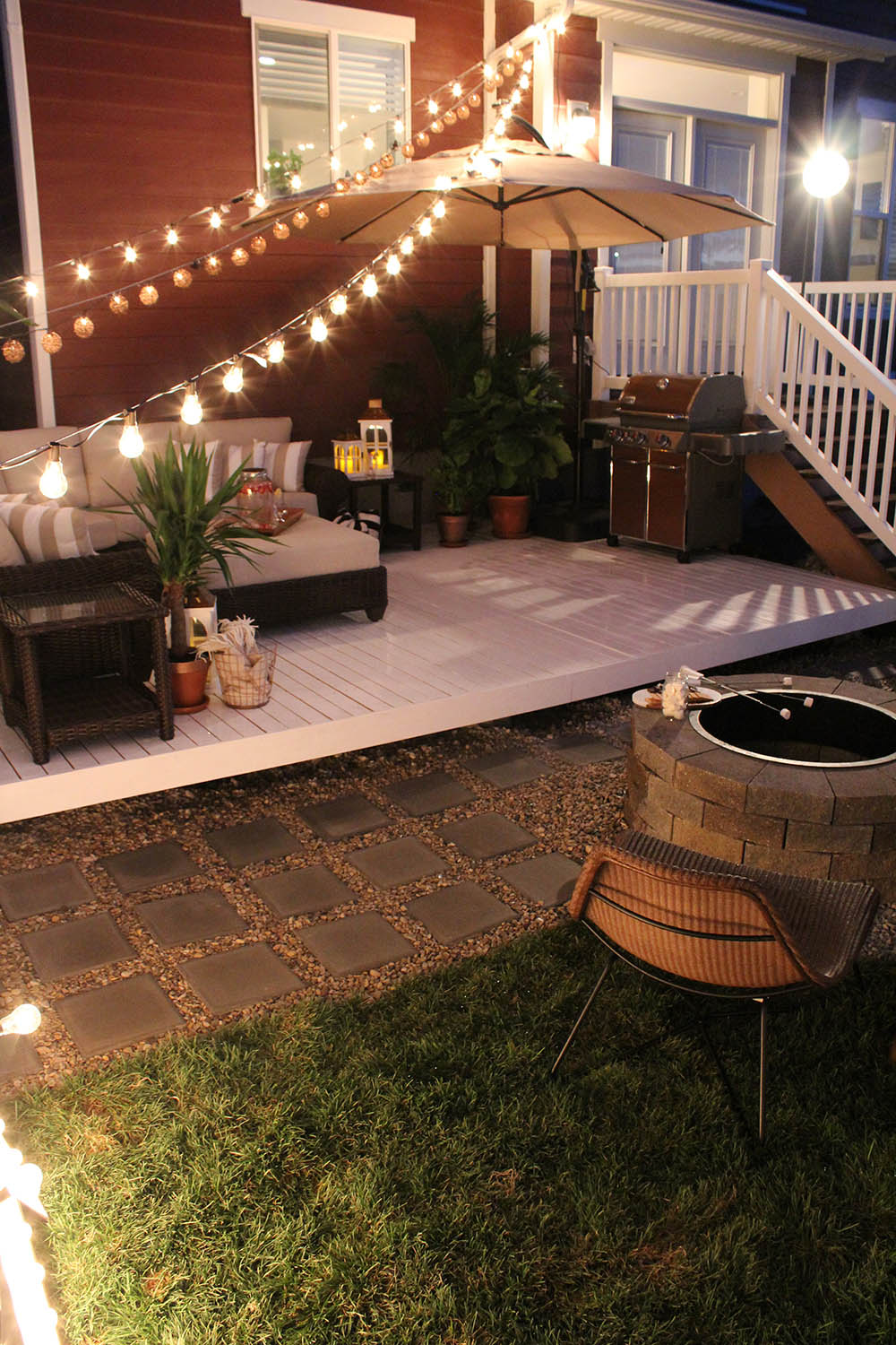 A fire pit and chair sit in front of a white low-level deck with a sectional.