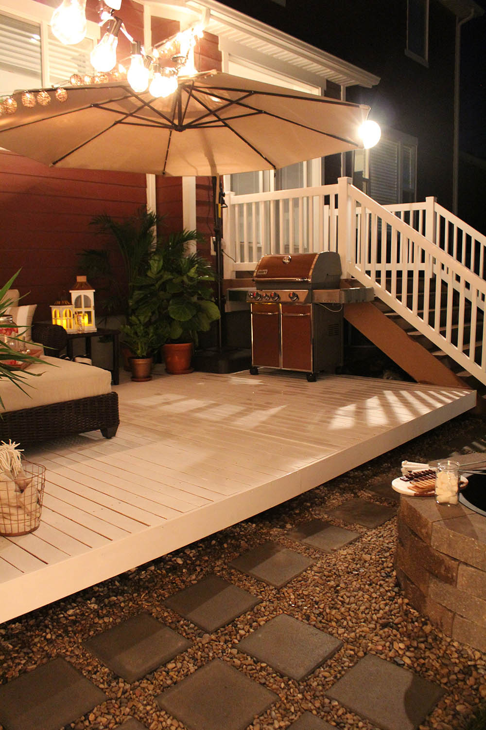 A grill sitting on a deck in front of an outdoor staircase.
