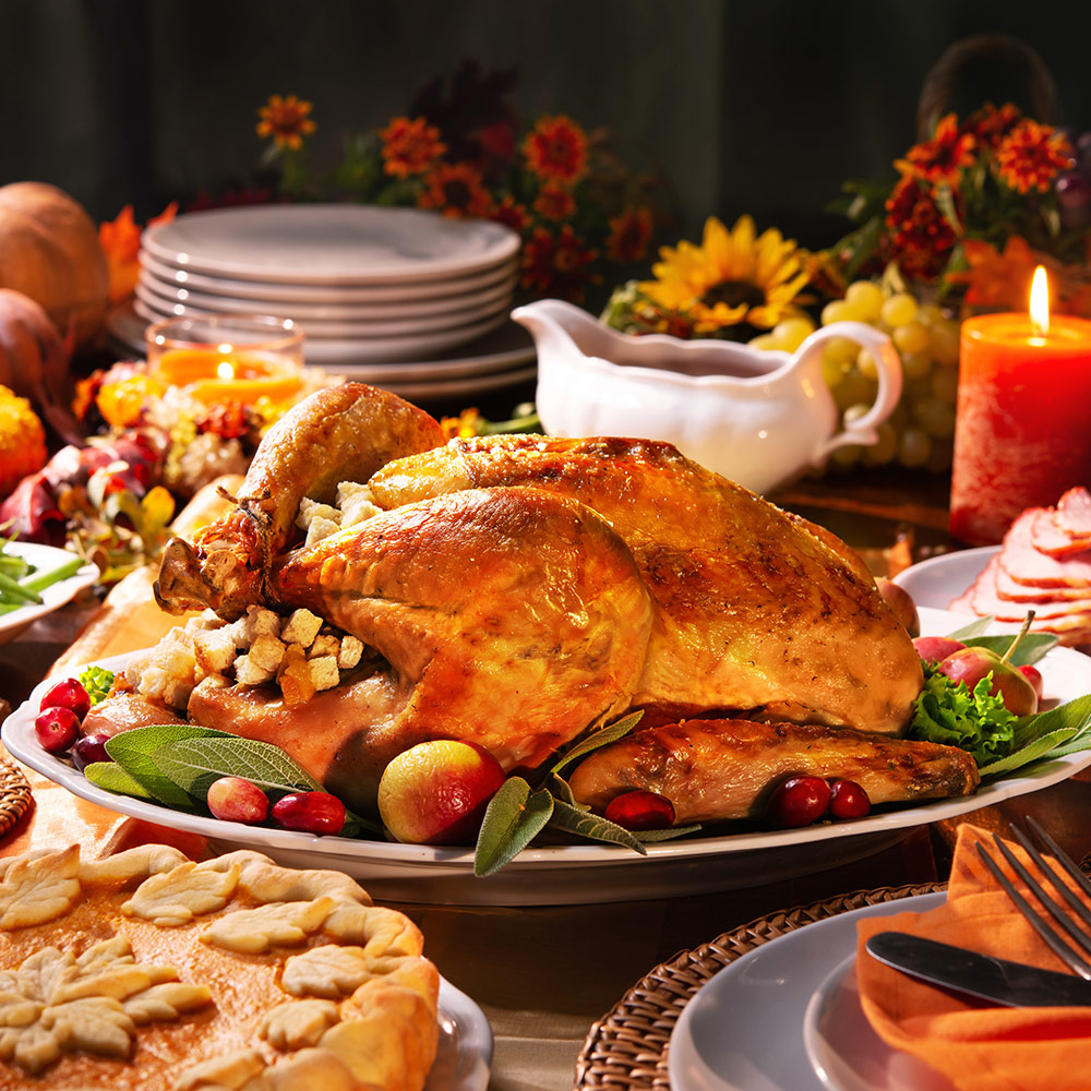 A turkey in the center of a table full of food.