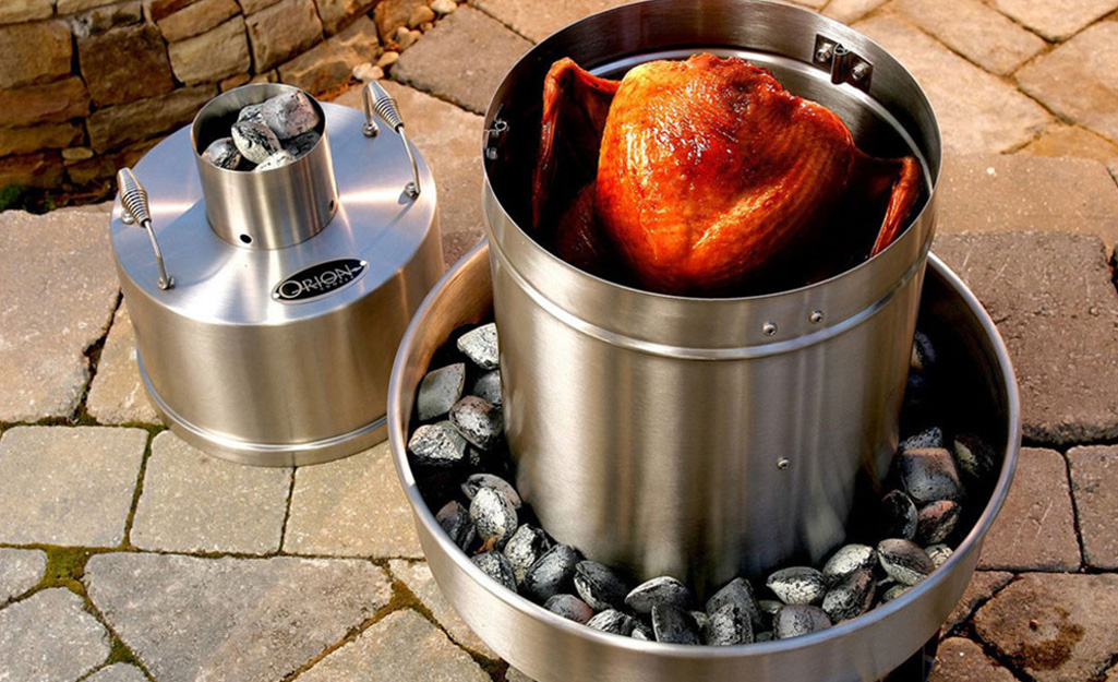 A turkey in a smoker on a patio.