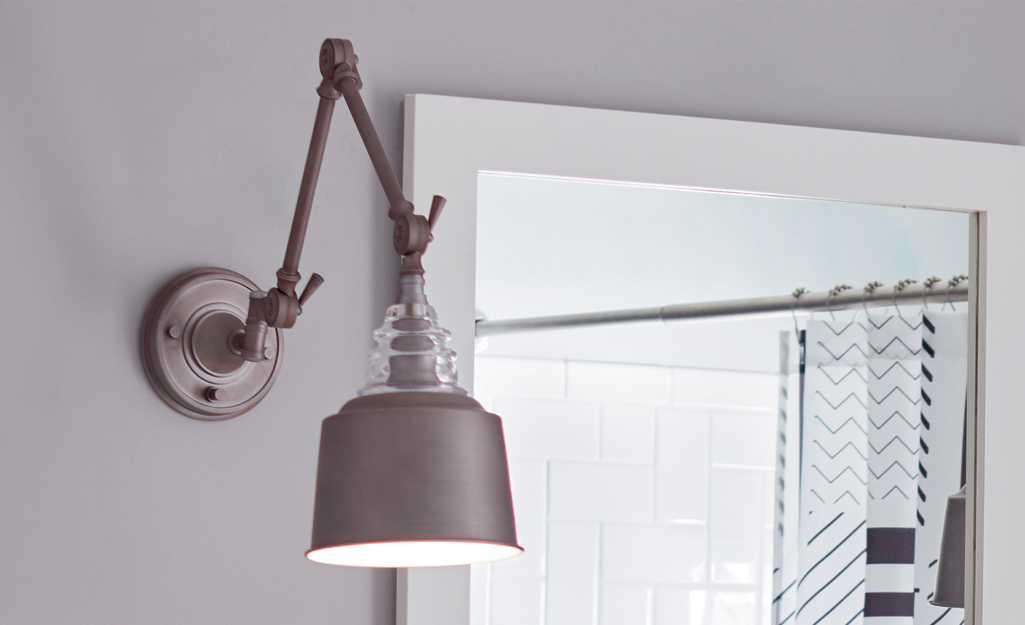 A silver light fixture next to a mirror.