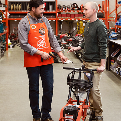 A Home Depot associate helping a customer with a tool rental.