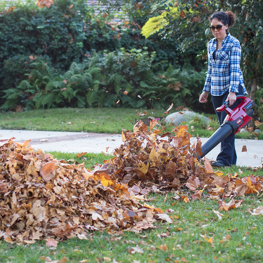 A woman uses a leaf blower in her front yard.