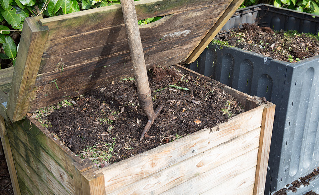 Leaves are added to a wooden bin with mulch,