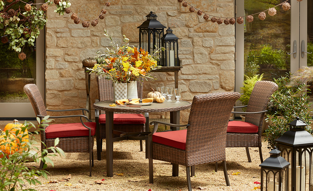 A patio with brick red patio furniture, string lights and fall decor.