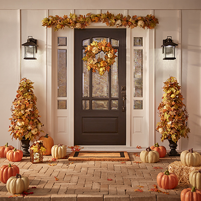 A front porch decorated with pumpkins and other fall decor.
