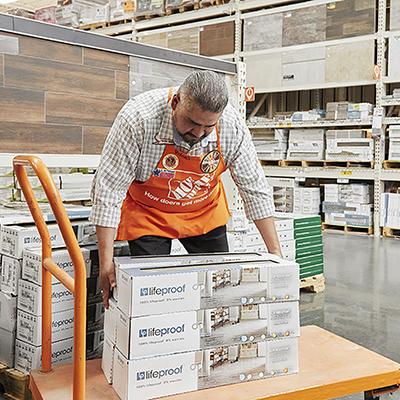 Proud customer watching The Home Depot Associate stack flooring.