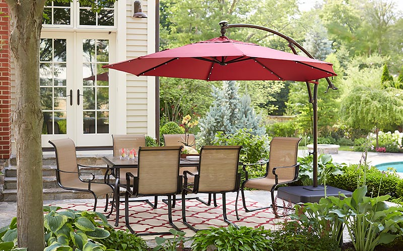 A red canopy patio umbrella covering a dining set