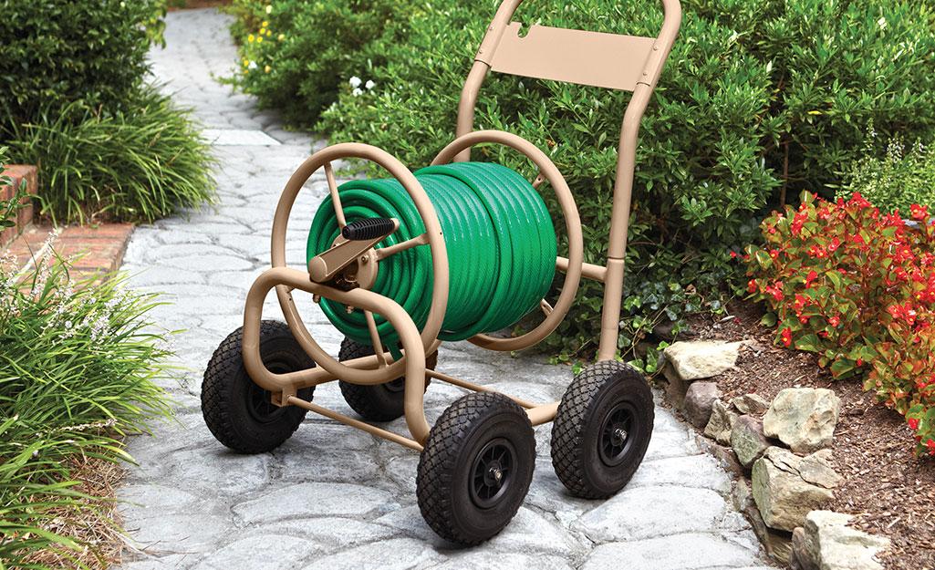 A hose reel cart on a stone garden path.