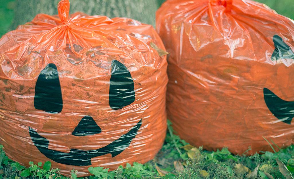 Festive pumpkin leaf bags sit on a lawn.