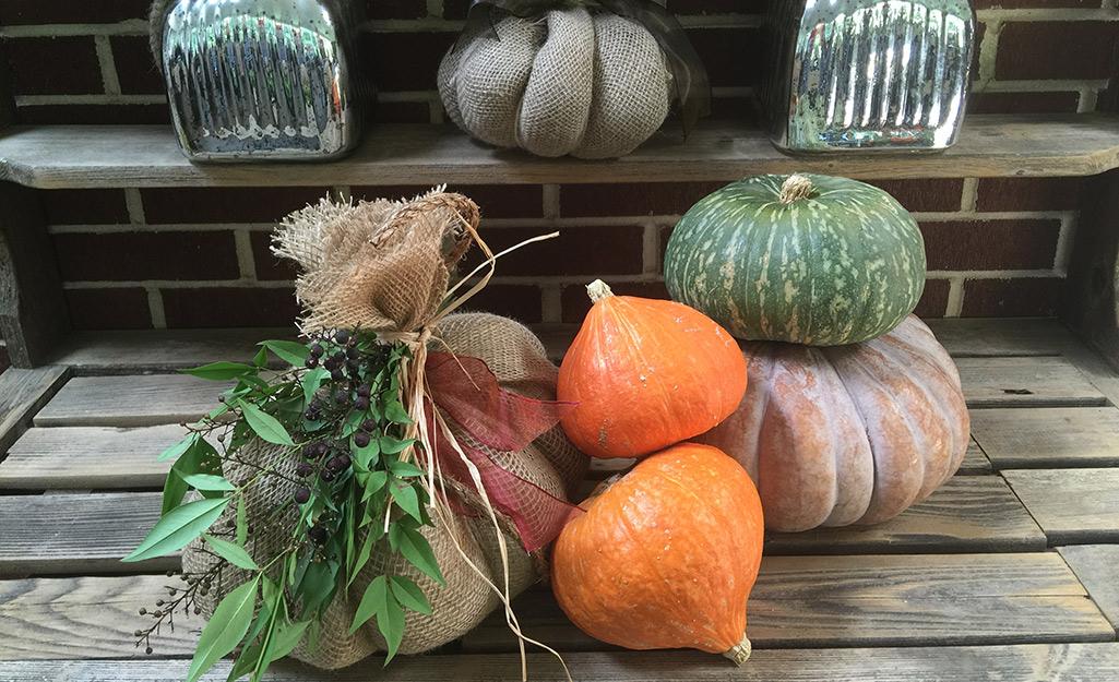 Burlap pumpkin next to a stack of live pumpkins.