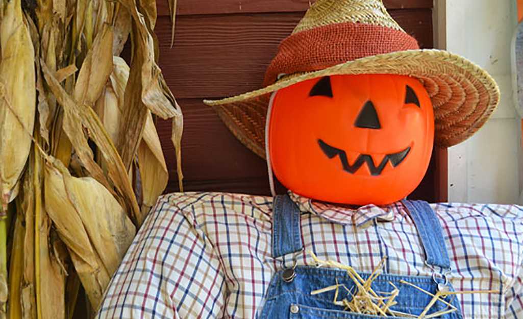 A scarecrow with a plastic pumpkin pail as a head.