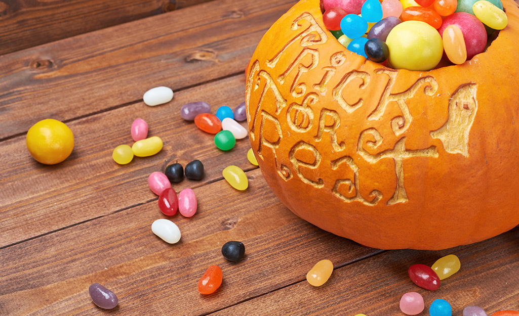 A candy bowl made from a carved live pumpkin.