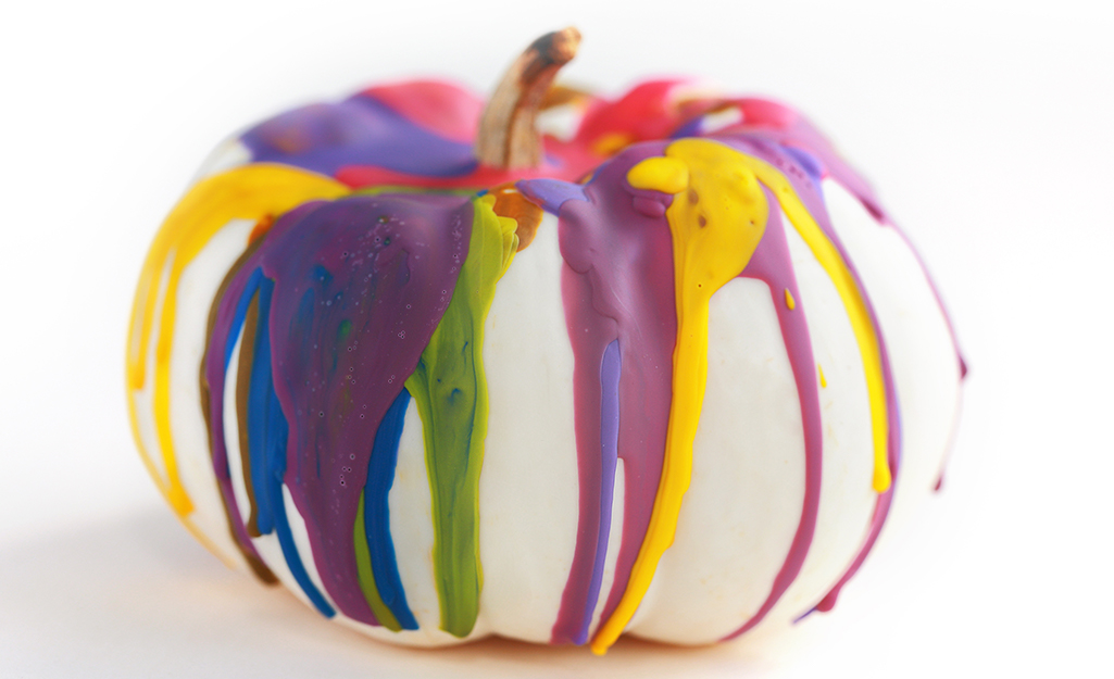 A white pumpkin covered with colorful crayon drips.