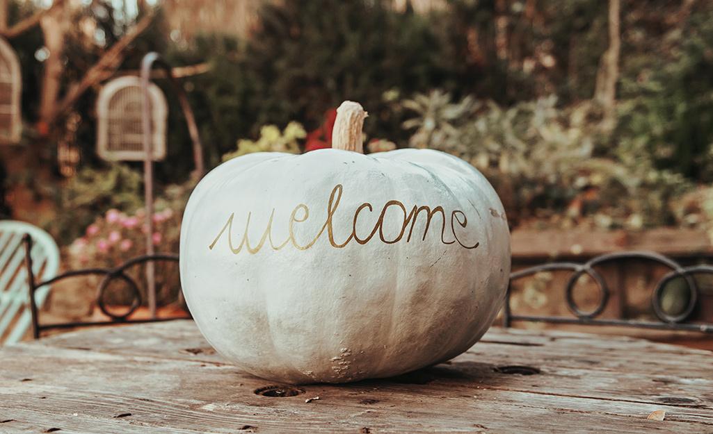 "A white pumpkin with ""welcome"" written across it in gold script."