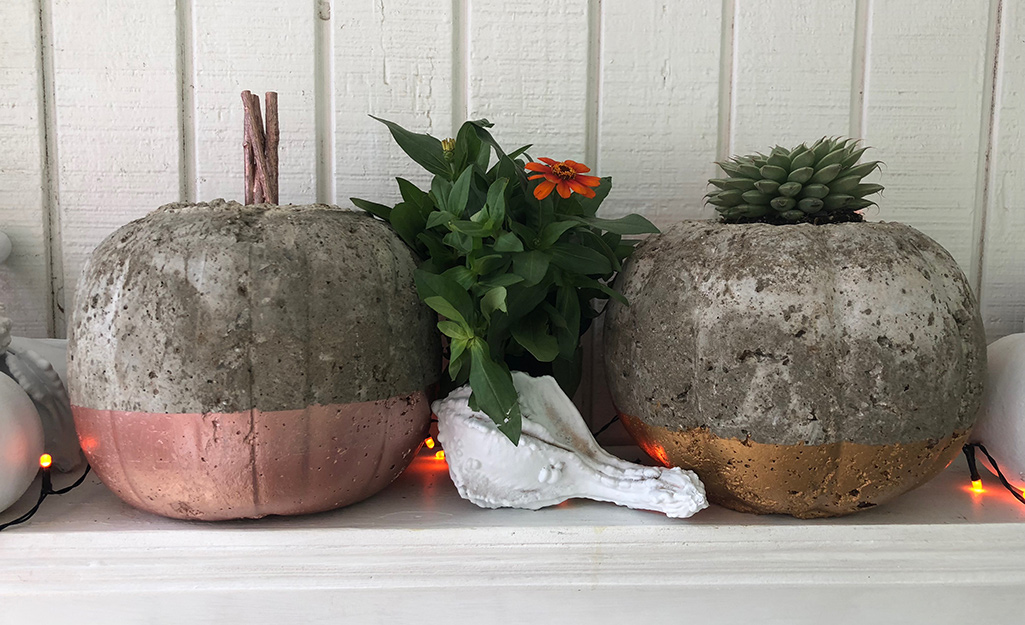 A mantle display of hypertufa pumpkins with metallic painted bottoms.