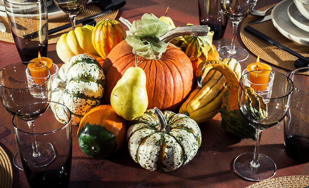 A stack of live pumpkins, gourds and pears used as a dining table centerpiece.