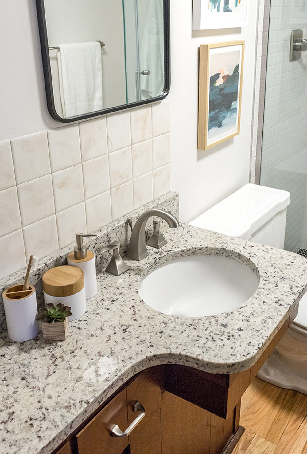 Marble bathroom countertop with a white hand towel, silver appliances and white soap dispenser, cream wall tile, a mirror and framed wall art.