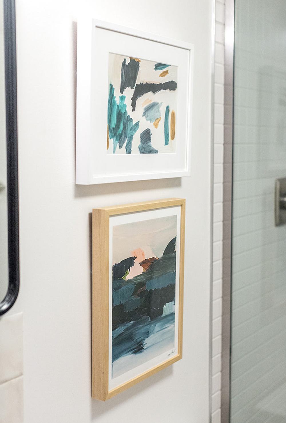 A white wall with two framed pieces of art work.