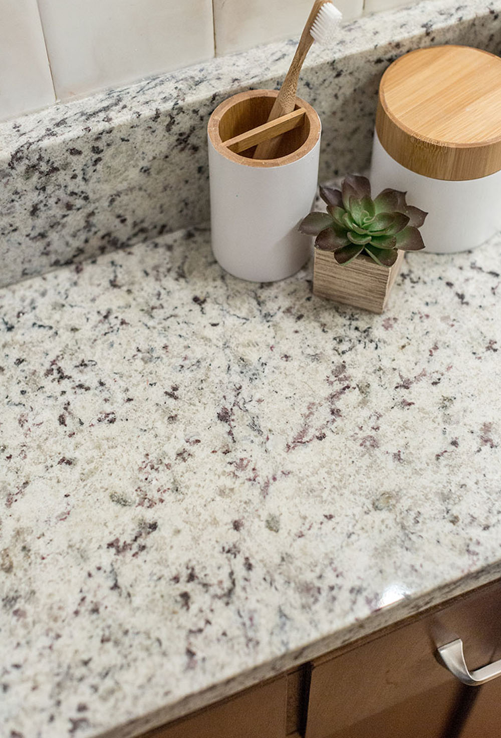 Marble countertop with a white toothbrush holder and a small plant.