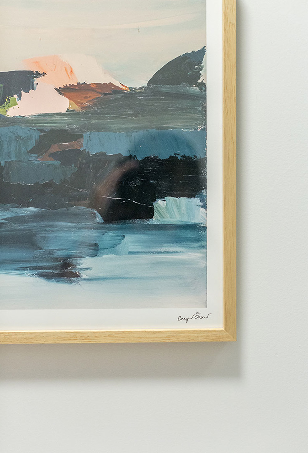 A painting in a wooden frame against a white wall.
