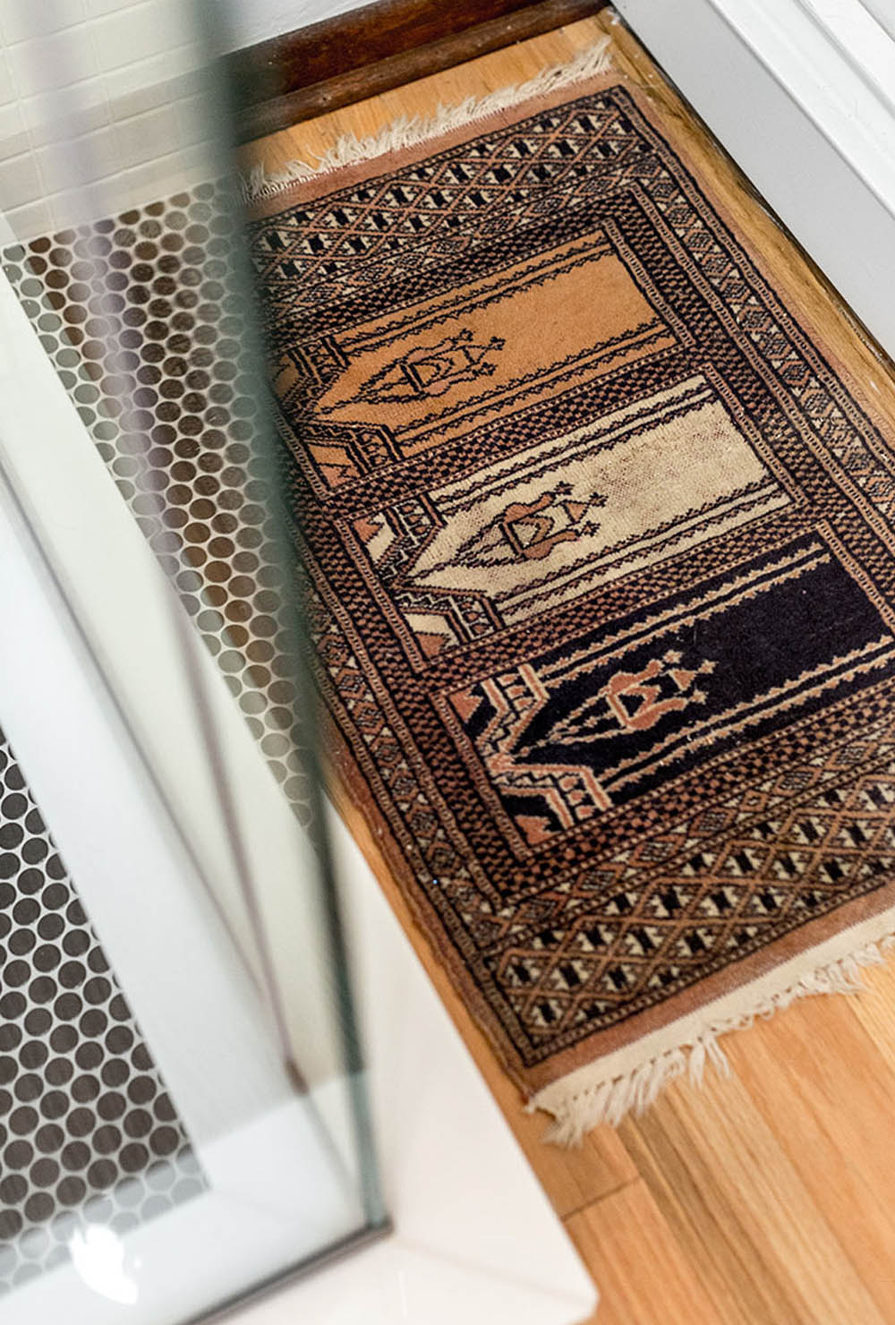 A brown patterned bath mat on wood flooring.