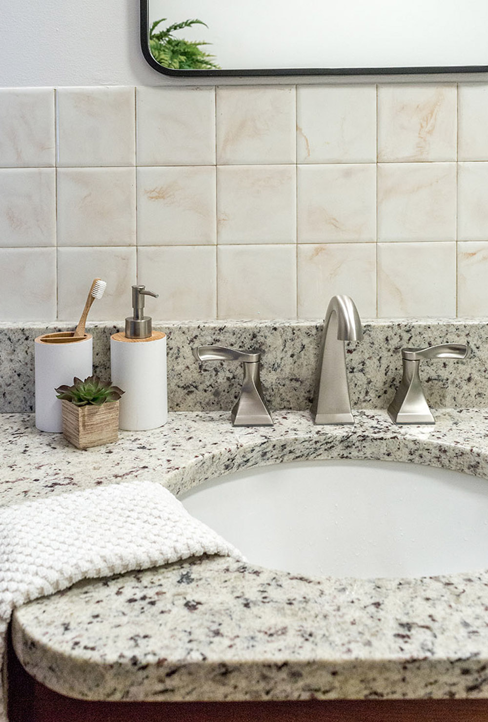 Marble bathroom countertop with a white hand towel, silver appliances and white soap dispenser, cream wall tile and a mirror.