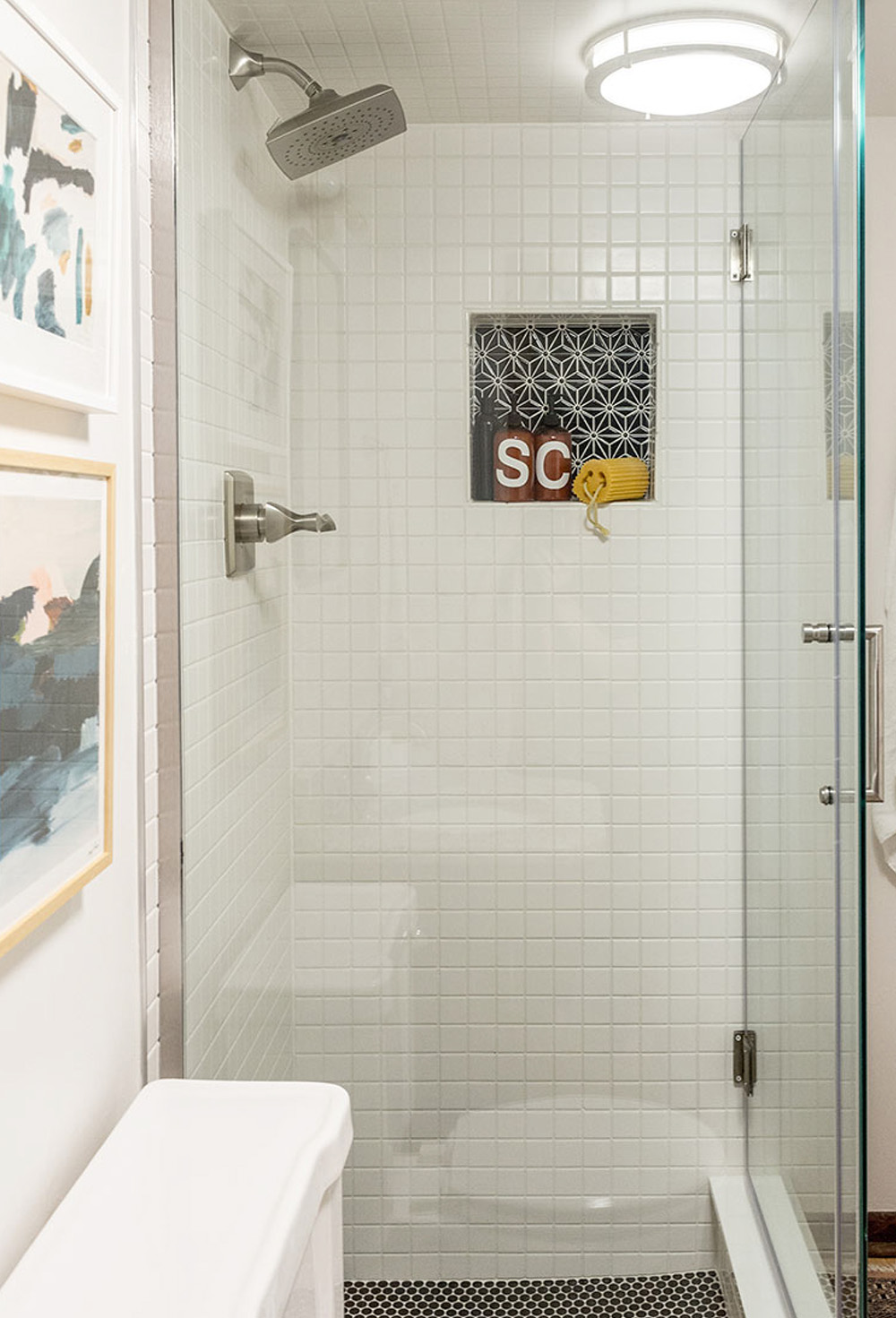 A glass shower with silver faucet and shower head.