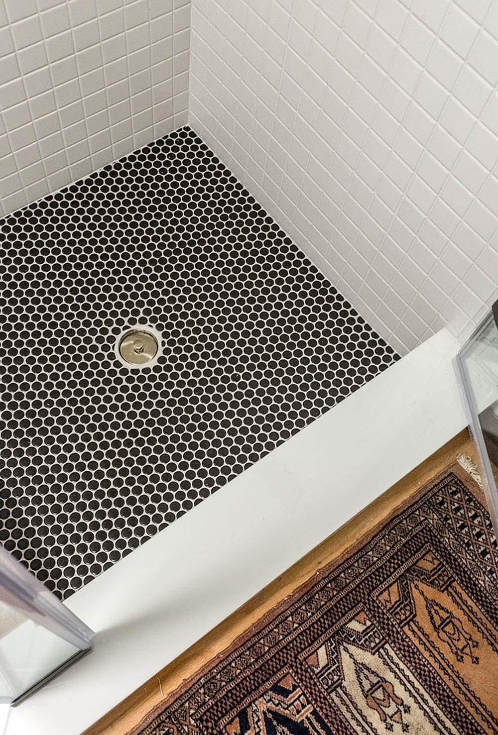 Black tiled shower floor.