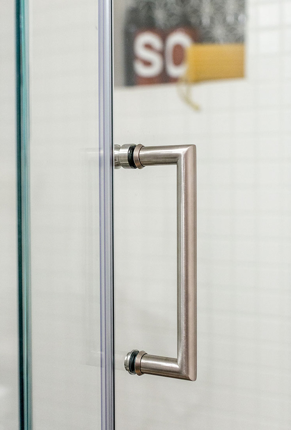A silver handle on a glass shower door.