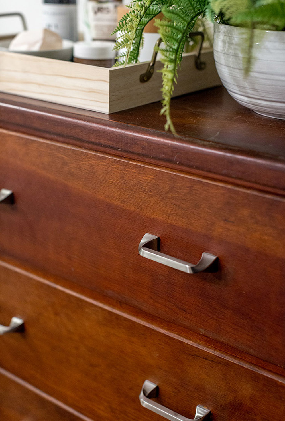 A wooden dresser with silver handles.