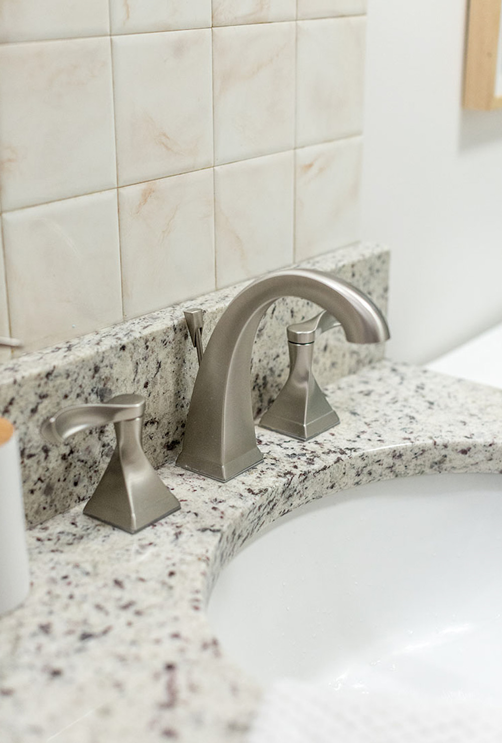A marble countertop with silver sink faucet against a beige tiled wall.