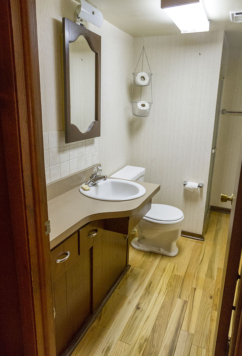 A bathroom with a brown vanity, white sink, white toilet, mirror and wood flooring.