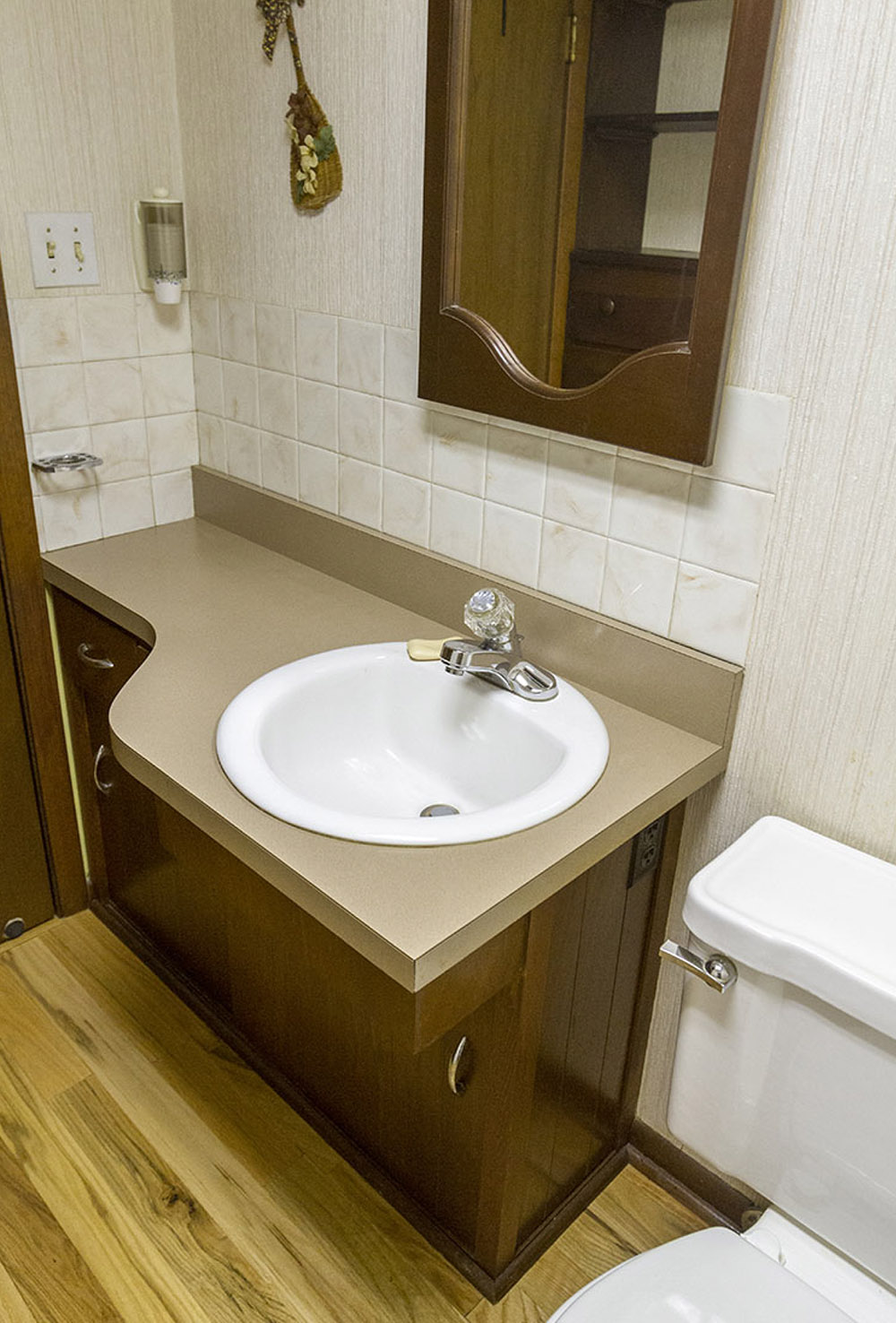 A brown bathroom vanity with a white sink against a beige wall with a mirror.