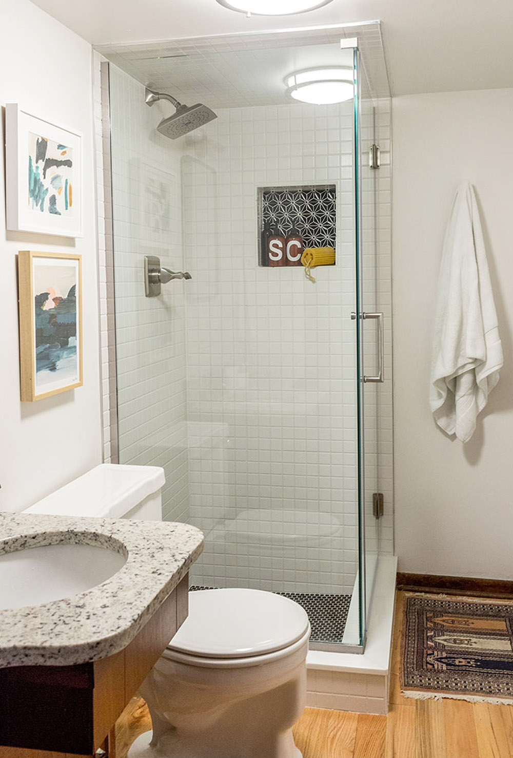 A bathroom with white walls, a glass shower, white toilet, wooden vanity, mirror, and gold bathroom light fixture.
