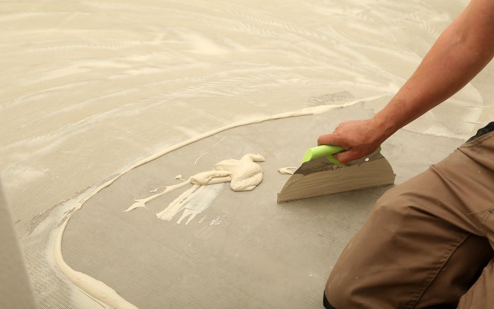 Man uses trowel to spread vinyl adhesive on concrete floor.