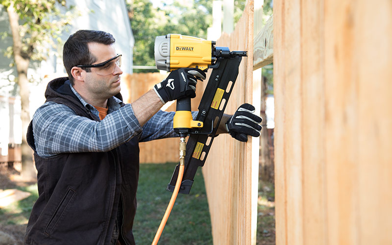 Man drilling a wood panel into a wood fence.