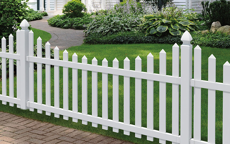A white vinyl fencing along a green yard.