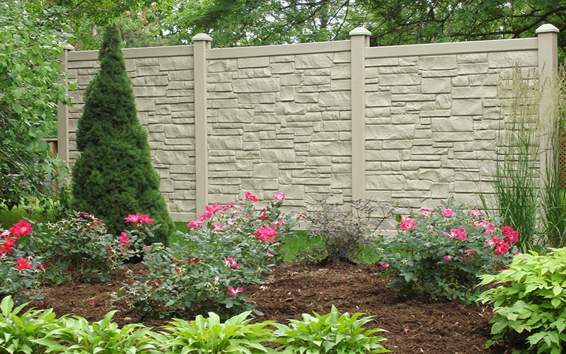 A gray composite fence with gate designed to look like stone.