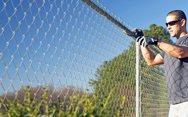 Man wearing work gloves installing a chain link fence.