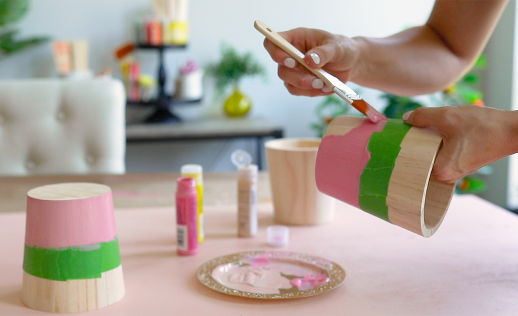 Một người phụ nữ đang vẽ những chiếc cốc gỗ để lấy một chiếc xô ăn sáng.