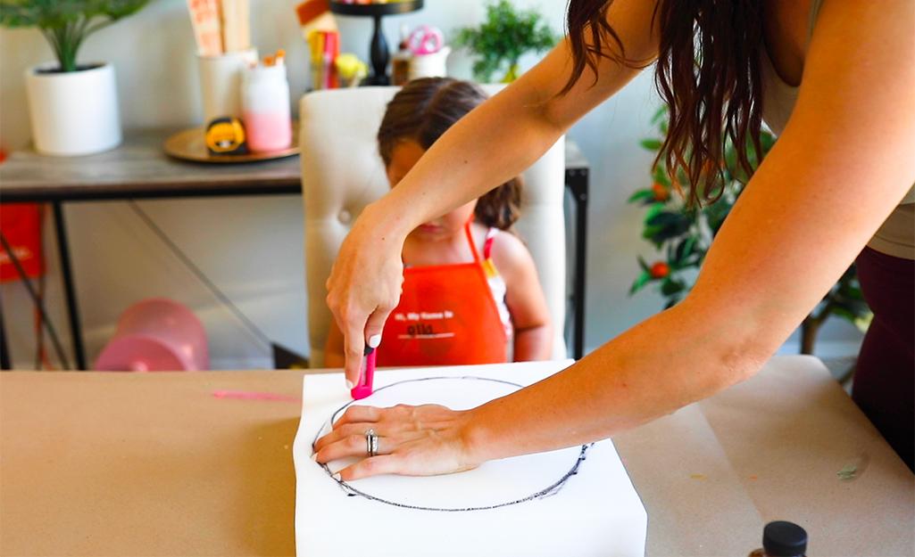 Một người phụ nữ đang cắt một hình tròn bằng xốp dài 10 inch cho một xô ăn nửa buổi.